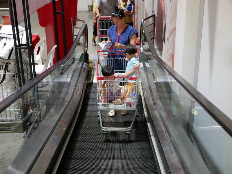 Een boodschappenwagentje op het winkelen karretjeroltrap met goederen en babys wordt gevuld die stock fotografie