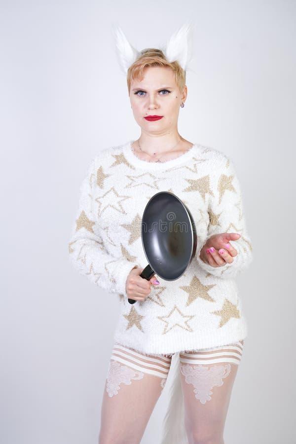 Een boos meisje met kort blondehaar in een pluizige sweater met bontoren kwaad plus groottevrouw met zwarte lege pan in hand o stock afbeeldingen
