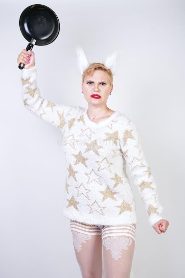 Een boos meisje met kort blondehaar in een pluizige sweater met bontoren kwaad plus groottevrouw met zwarte lege pan in hand o royalty-vrije stock foto's
