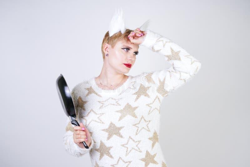 Een boos meisje met kort blondehaar in een pluizige sweater met bontoren kwaad plus groottevrouw met zwarte lege pan in hand o stock foto