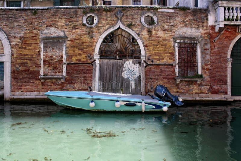 Een boot die dichtbij een dldbakstenen muur wordt vastgelegd in Venetië stock afbeelding