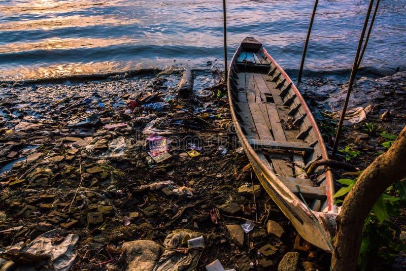 Een boot en avondgetijde op slordige riverbank bij zonsondergang royalty-vrije stock afbeeldingen