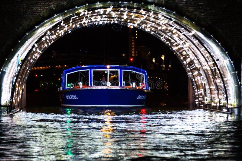 Een boot gaat door een licht gevulde tunnel in Onder- Amsterdam over, stock fotografie