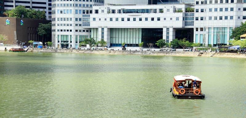 Een boot navigeert de rivier van Singapore stock afbeelding