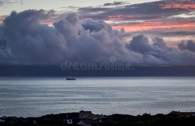 Een boot op het overzees onder de hemel met de het plaatsen zon op de kust stock fotografie