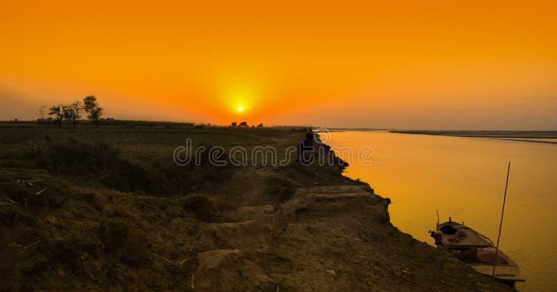 Een boot op een rivierbank in zonsondergangtijd royalty-vrije stock fotografie
