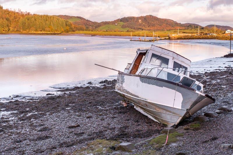 Een boot van de motorkruiser ligt op de modder wachtend op het getijde om in Kippford, dichtbij Dalbeattie, in Dumfries en Gallow stock afbeelding