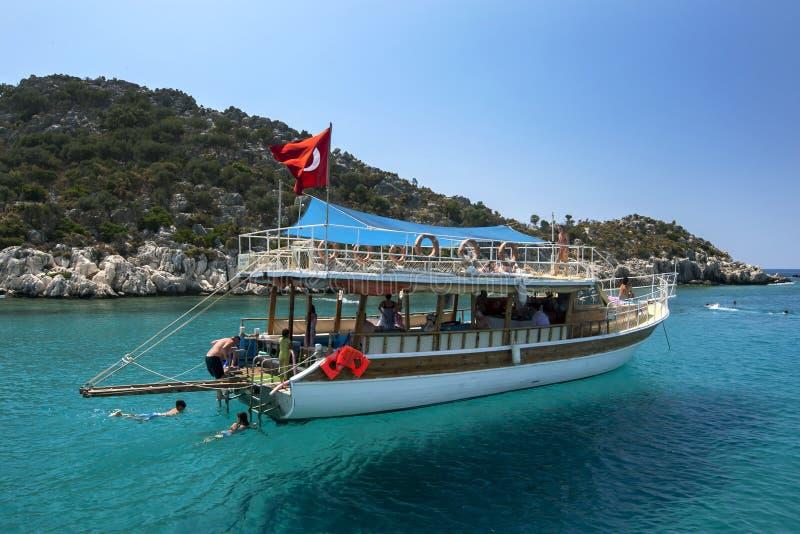 Een boot van de toeristencruise verankerde naast de Gedaalde Stad van Simena stock afbeeldingen