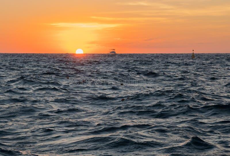 Download Een Boot In Veranderlijke Overzees Bij Zonsondergang Stock Afbeelding - Afbeelding bestaande uit roeien, golven: 107703273