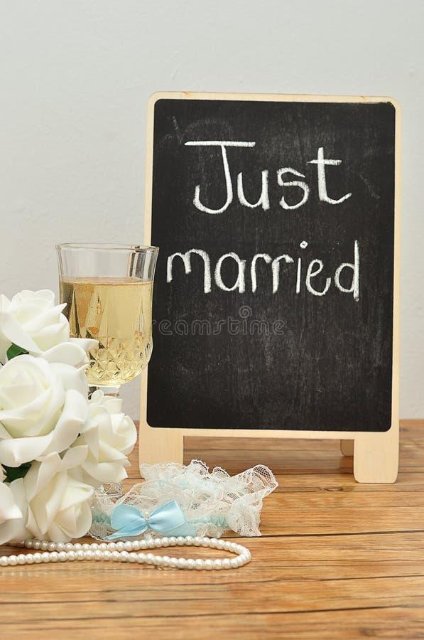 Een bord met enkel gehuwd op het getoond met een glas champagne, een bos van rozen en een kouseband stock foto's