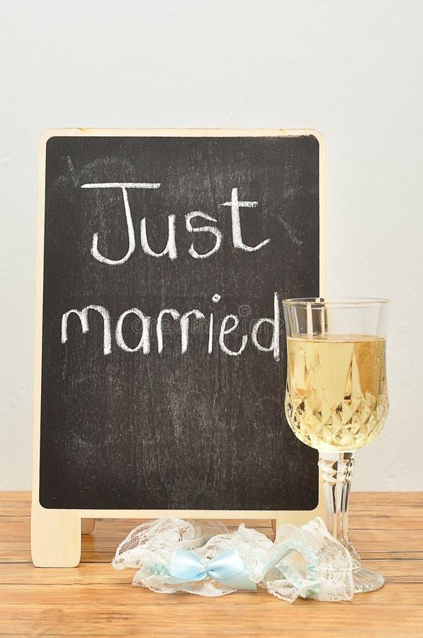 Een bord met enkel gehuwd op het getoond met een glas van champagne en een kouseband stock foto