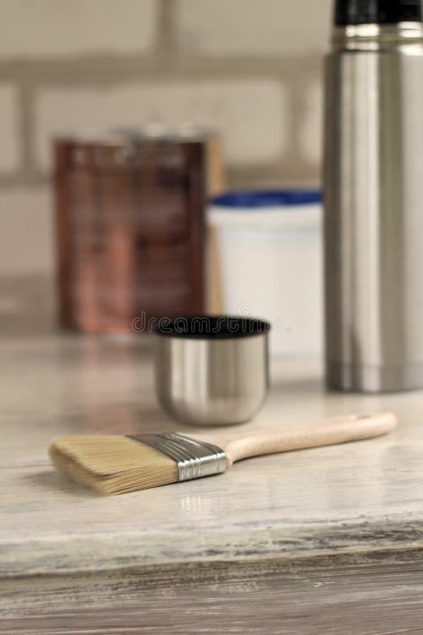 Een borstel ligt naast een plastic verfemmer met een blauw deksel, kan een metaal, een thermosfles met een kop op oude witte uits stock foto