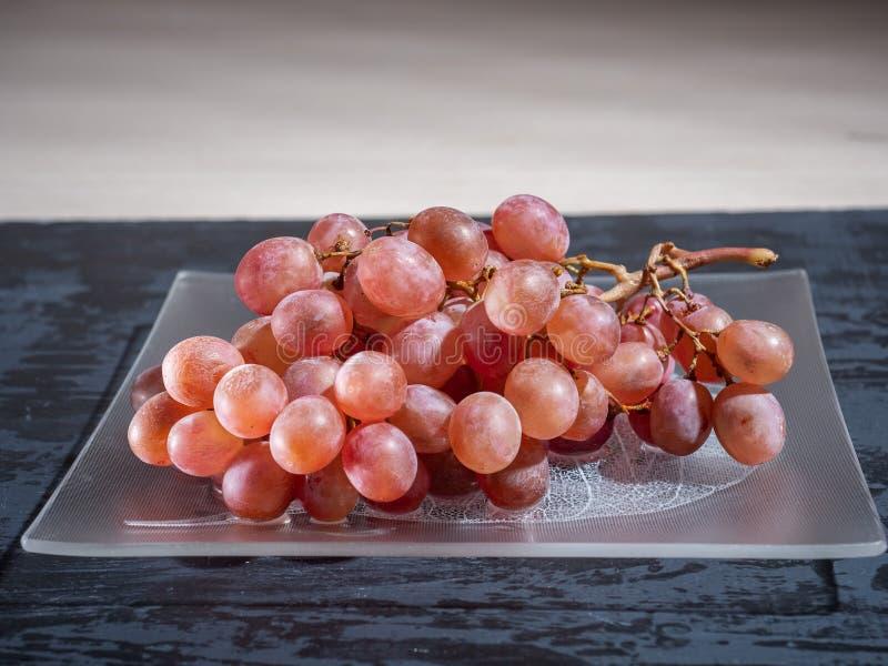 Een borstel van roze druiven op een glasplaat, donkere achtergrond Zachte nadruk royalty-vrije stock foto's