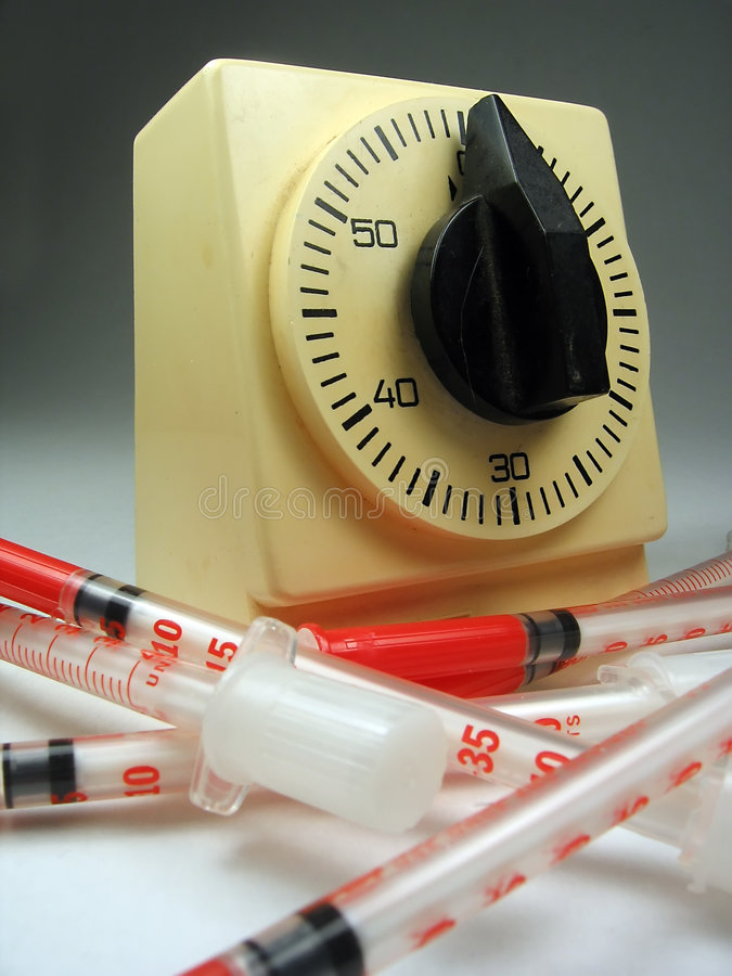 Een bos van drugs, spuiten die een chronometer omringen stock fotografie