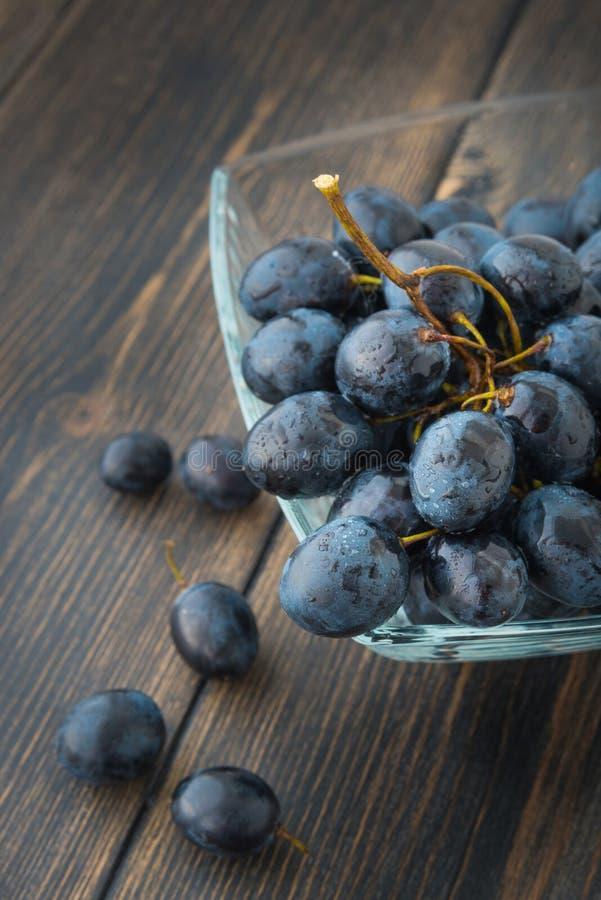 Een bos van druiven - zwarte Spaanse druif - in een glaskom royalty-vrije stock afbeelding