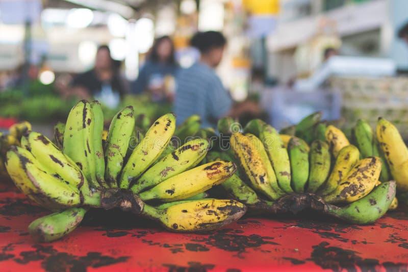 Een bos van middelgrote ruwe en rijpe gecultiveerde banaan op organische lokale markt stock foto's