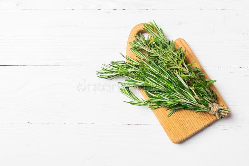 Een bos van verse geurige rozemarijn op een knipselraad op een houten witte achtergrond De ruimte van het exemplaar Vlakke lay-ou stock fotografie