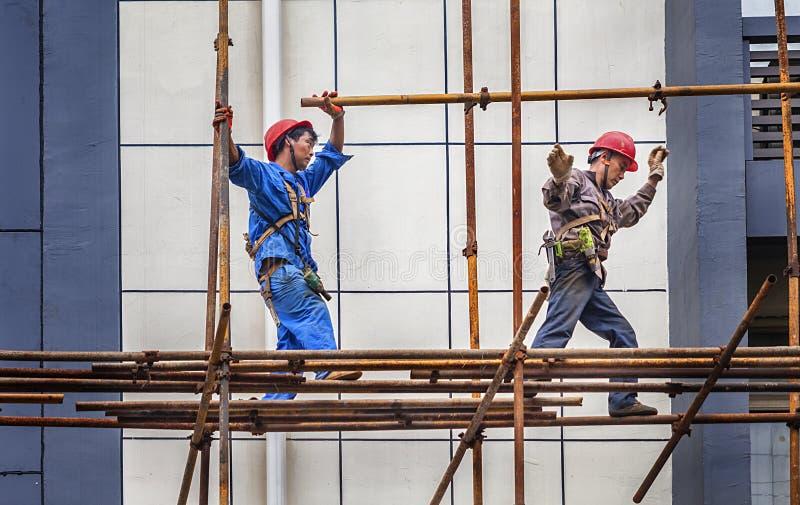 Een bouwer die op een steiger lopen