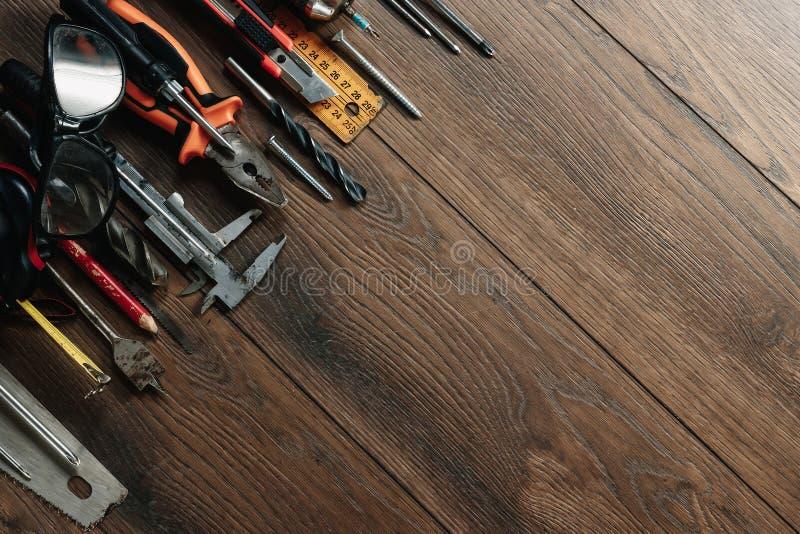 Een bouwhulpmiddel op een bruine houten achtergrond Mening van hierboven Beeldachtergrond, screensaver Het concept bouw, r royalty-vrije stock fotografie