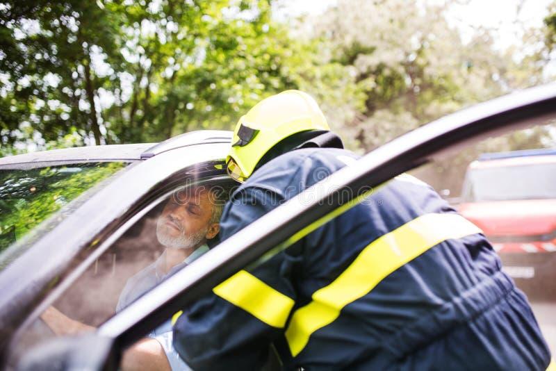 Een brandbestrijder die een onbewuste mens krijgen uit de auto na een ongeval royalty-vrije stock foto