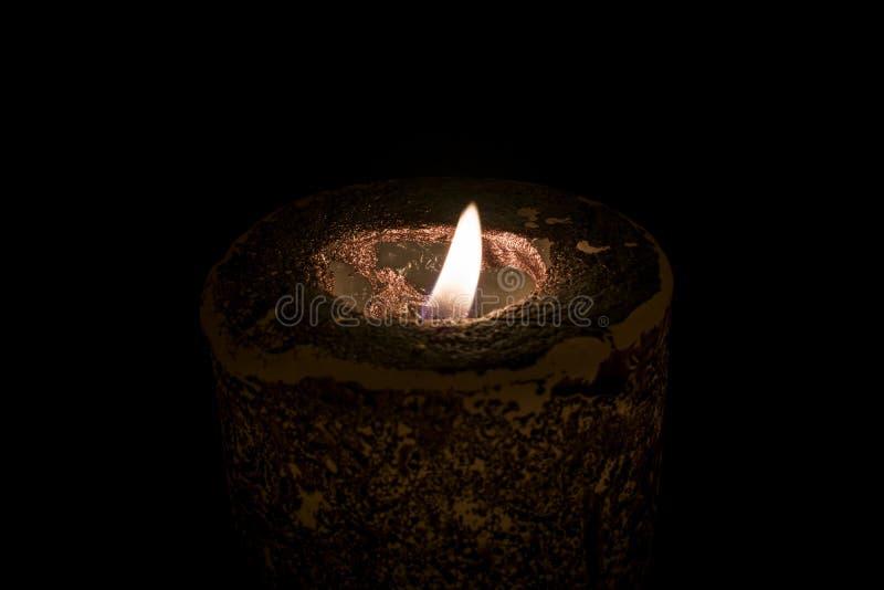 Een brandende kaars in dark royalty-vrije stock afbeeldingen