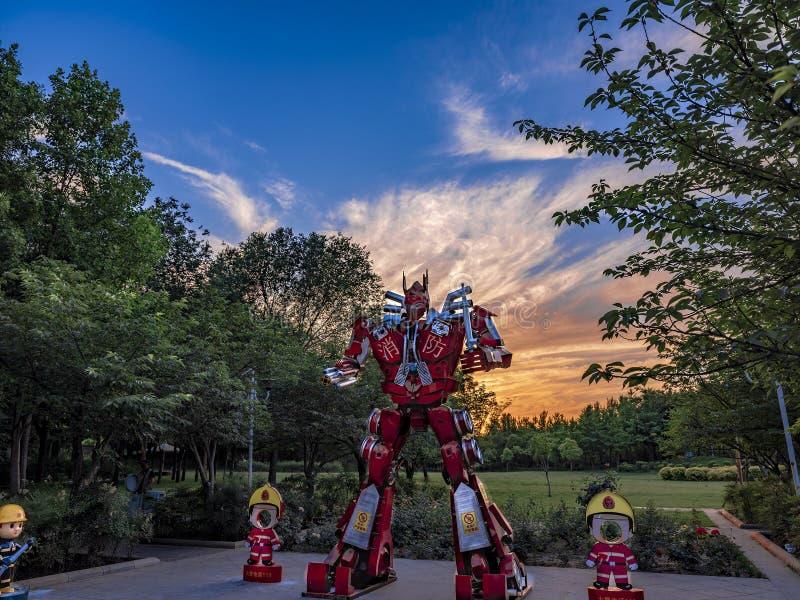 Een Brandrobot die zich met kleurrijke hemel bevinden stock afbeeldingen