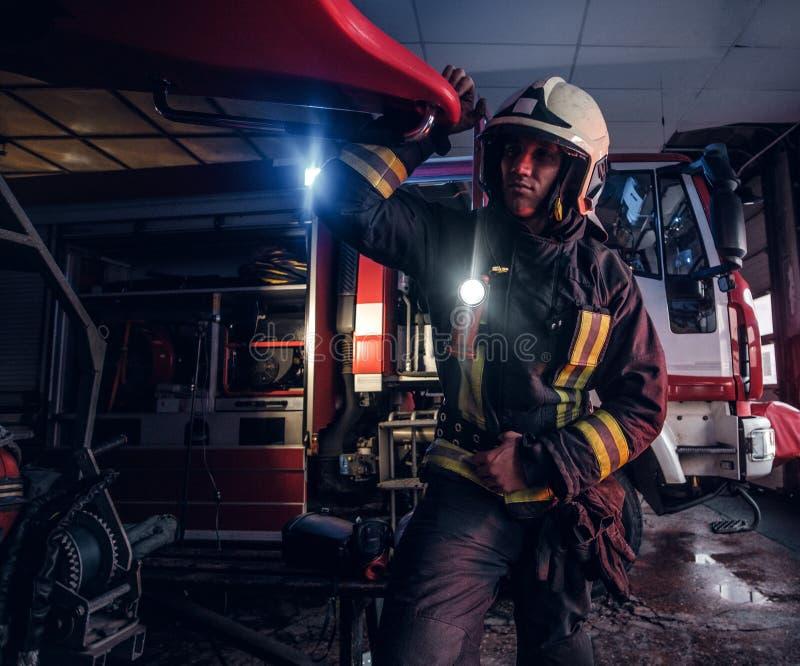 Een brandweerman die een beschermend uniform met flitslicht dragen omvatte het werken in een brandweerkazernegarage royalty-vrije stock foto