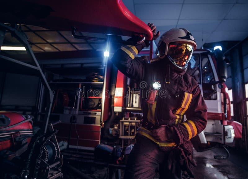 Een brandweerman die een beschermend uniform met flitslicht dragen omvatte het werken in een brandweerkazernegarage stock afbeeldingen