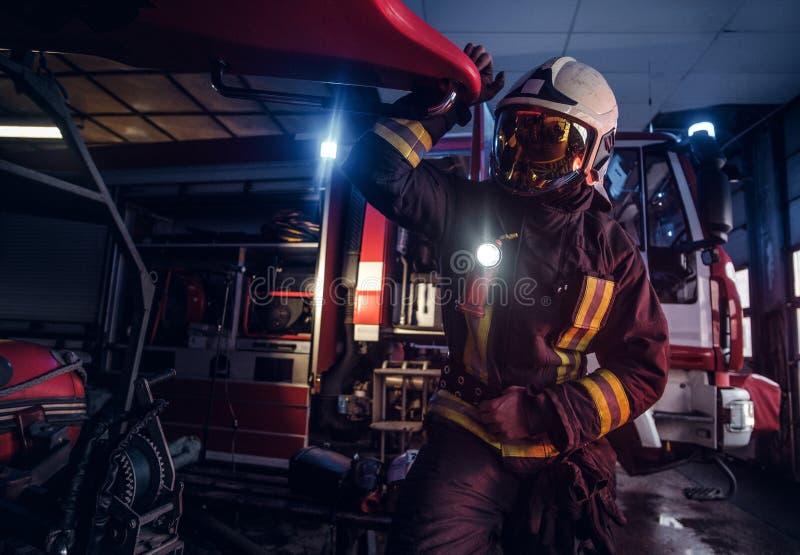 Een brandweerman die een beschermend uniform met flitslicht dragen omvatte het werken in een brandweerkazernegarage royalty-vrije stock afbeelding