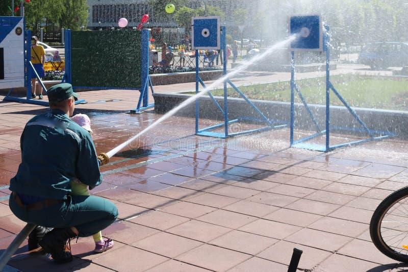 Een brandweerman` s mens onderwijst een kind, een meisje om een brand te doven door een stroom van water van een bronzboyt, een b royalty-vrije stock fotografie