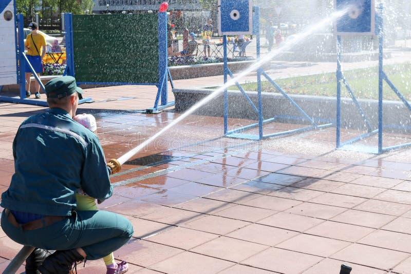 Een brandweerman` s mens onderwijst een kind, een meisje om een brand te doven door een stroom van water van een bronzboyt, een b royalty-vrije stock afbeeldingen