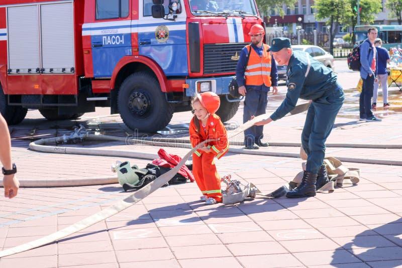 Een brandweerman` s mens onderwijst een klein meisje in een ornery vuurvast kostuum om rond met Wit-Rusland, Minsk, 08 te lopen 0 stock afbeeldingen