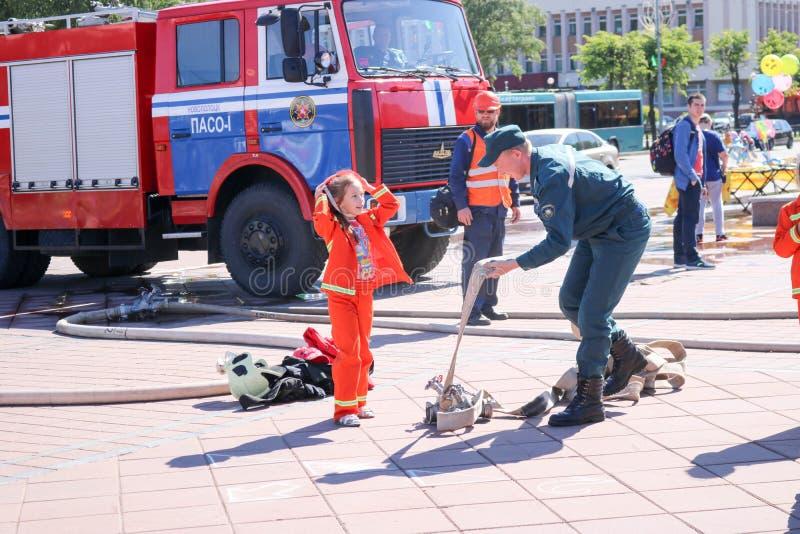 Een brandweerman` s mens onderwijst een klein meisje in een ornery vuurvast kostuum om rond met Wit-Rusland, Minsk, 08 te lopen 0 royalty-vrije stock foto