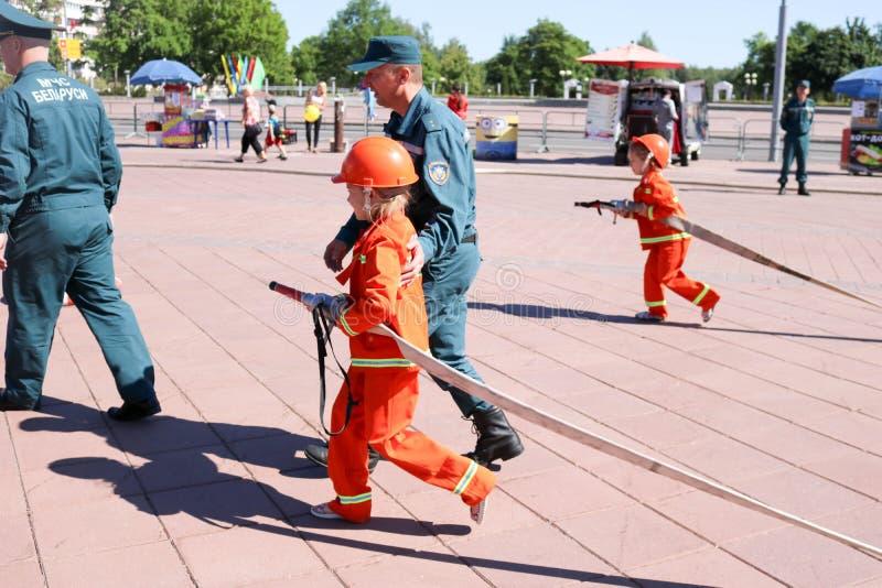 Een brandweerman` s mens onderwijst een klein meisje in een ornery vuurvast kostuum om rond met Wit-Rusland, Minsk, 08 te lopen 0 stock foto