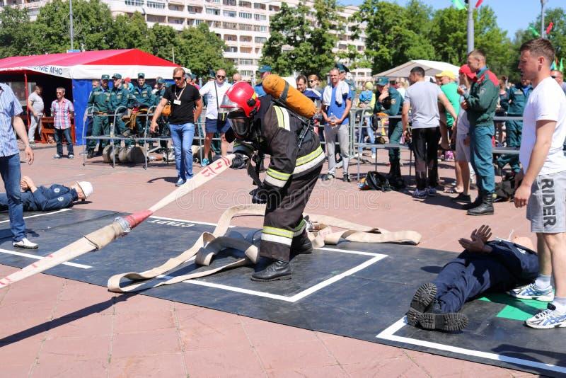 Een brandweerman in een vuurvast kostuum en een helm die een brandslang houden bij de concurrentie van de brandsport Minsk, Wit-R royalty-vrije stock afbeelding