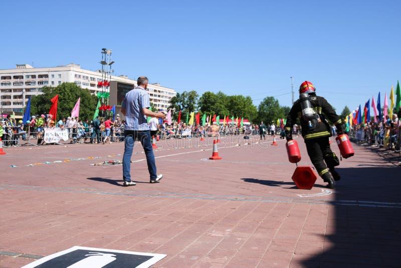 Een brandweerman in een vuurvast kostuum en een helm doven een brand bij de concurrentie van de brandsport, Wit-Rusland, Minsk, 0 royalty-vrije stock foto