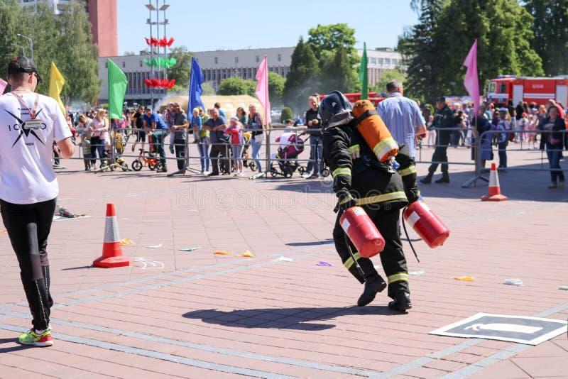 Een brandweerman in een vuurvast kostuum en een helm doven een brand bij de concurrentie van de brandsport, Wit-Rusland, Minsk, 0 stock fotografie