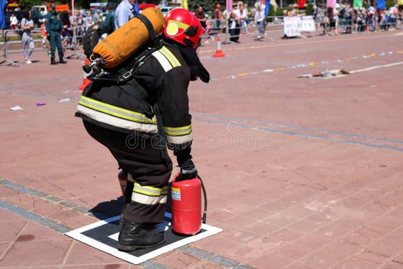 Een brandweerman in een vuurvast kostuum en een helm loopt met rode brandblusapparaten om een brand te doven stock afbeelding
