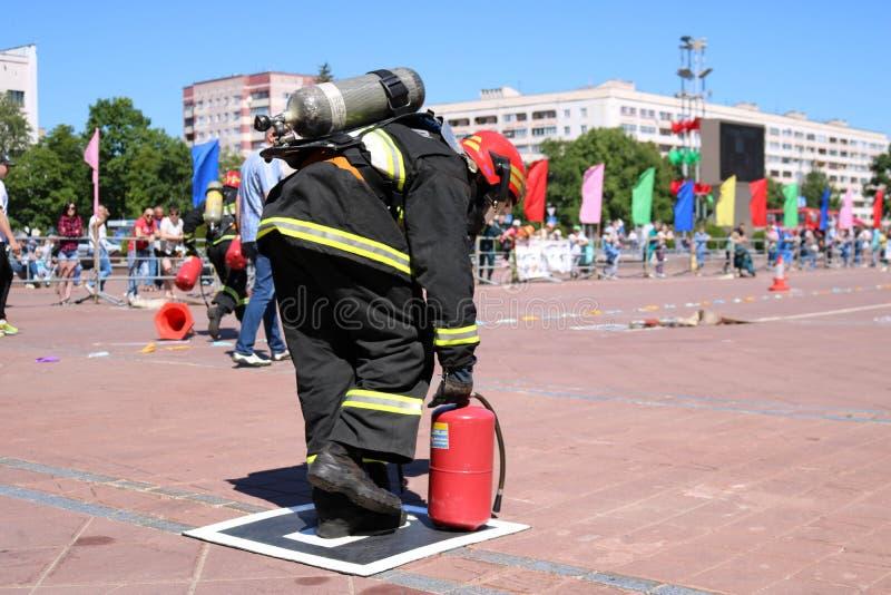 Een brandweerman in een vuurvast kostuum en een helm loopt met rode brandblusapparaten om een brand te doven stock afbeeldingen