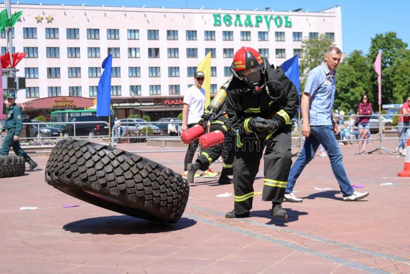 Een brandweerman in een vuurvast kostuum stelt en draait een groot rubberwiel in de brandbestrijdingsconcurrentie in werking, Wit royalty-vrije stock foto