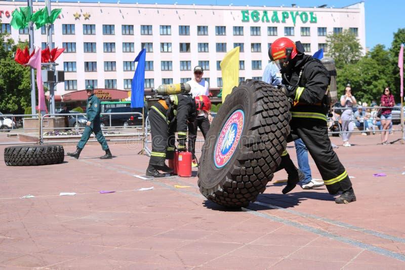 Een brandweerman in een vuurvast kostuum stelt en draait een groot rubberwiel in de brandbestrijdingsconcurrentie in werking, Wit royalty-vrije stock foto's