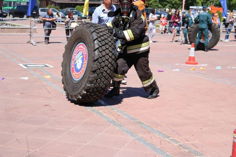Een brandweerman in een vuurvast kostuum stelt en draait een groot rubberwiel in de brandbestrijdingsconcurrentie in werking, Wit stock afbeeldingen