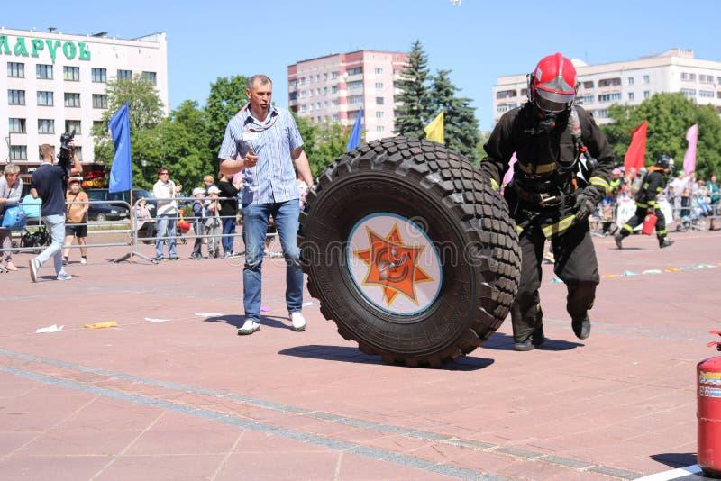 Een brandweerman in een vuurvast kostuum stelt en draait een groot rubberwiel in de brandbestrijdingsconcurrentie in werking, Wit royalty-vrije stock fotografie