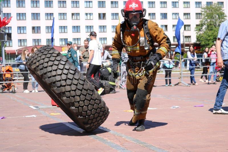 Een brandweerman in een vuurvast kostuum stelt en draait een groot rubberwiel in de brandbestrijdingsconcurrentie in werking, Wit stock foto's