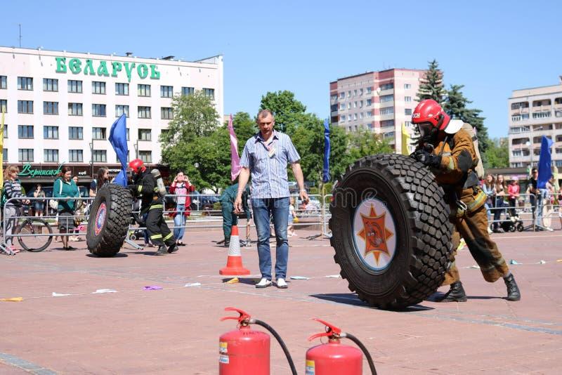 Een brandweerman in een vuurvast kostuum stelt en draait een groot rubberwiel in de brandbestrijdingsconcurrentie in werking, Wit royalty-vrije stock afbeeldingen