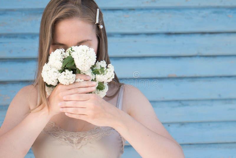 Een breekbaar blond haarmeisje behandelt haar gezicht met een klein boeket van witte bloemen, lang haar met haarspelden met parel royalty-vrije stock foto