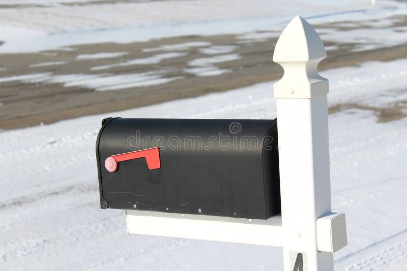 Een brievenbus overziet een sneeuw behandelde rijweg royalty-vrije stock afbeeldingen