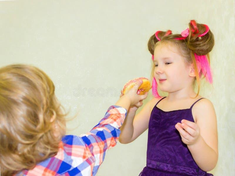 Een broer en een zuster, een meisje en een jongen, spelen met een doughnut en voeden elkaar bij een partij stock fotografie