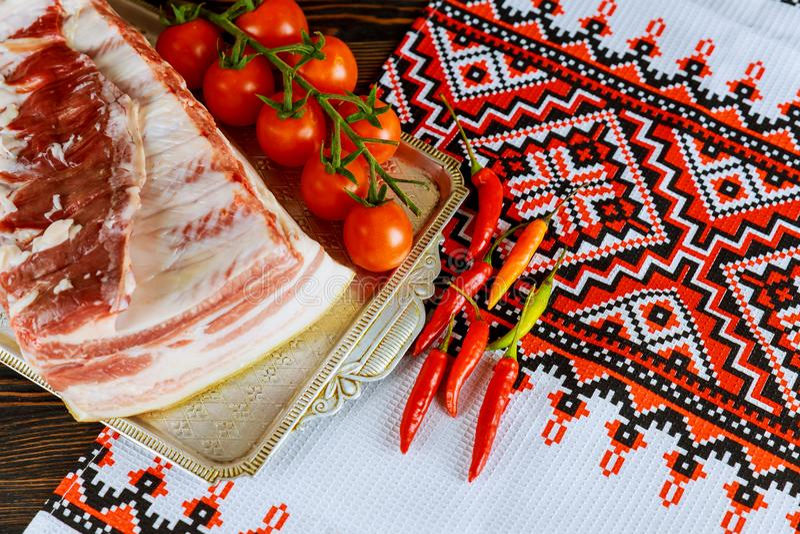 Een brok van bacon dat met kruiden en kruiden op een document met gemarineerde tomaten wordt gebakken stock afbeelding
