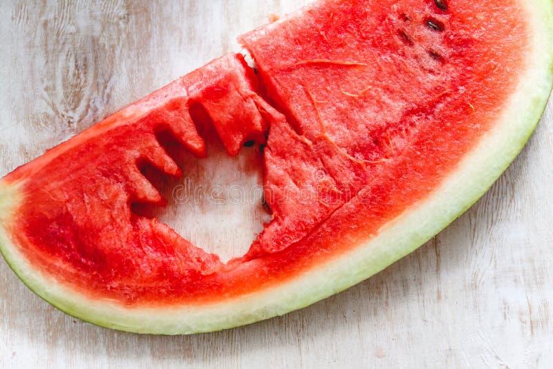 Een brok van sappige rode watermeloen met de hand van een kind sneed daarin op een lichte achtergrond Close-up royalty-vrije stock afbeeldingen